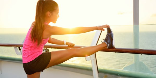 Fitness girl stretching leg on cruise vacation. Young woman adul