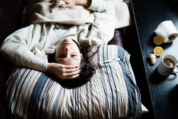 Sick young woman in bed at home having flu,measuring temperature