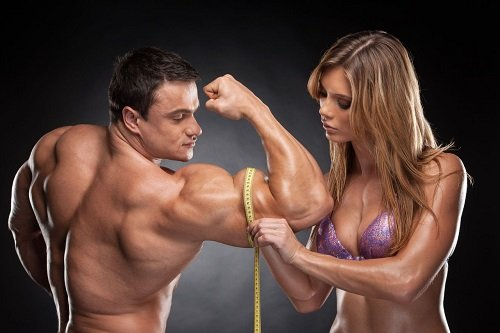 Woman Measuring Man's Bicep