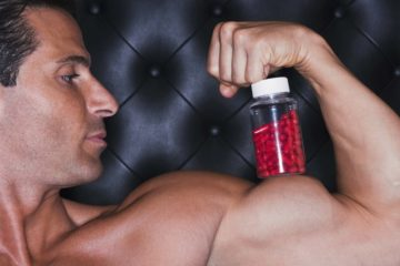 Man Balancing Bottle Of Pills On Bicep