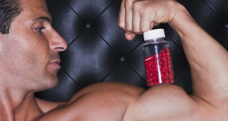 Man Balancing Bottle Of Pills On Bicep